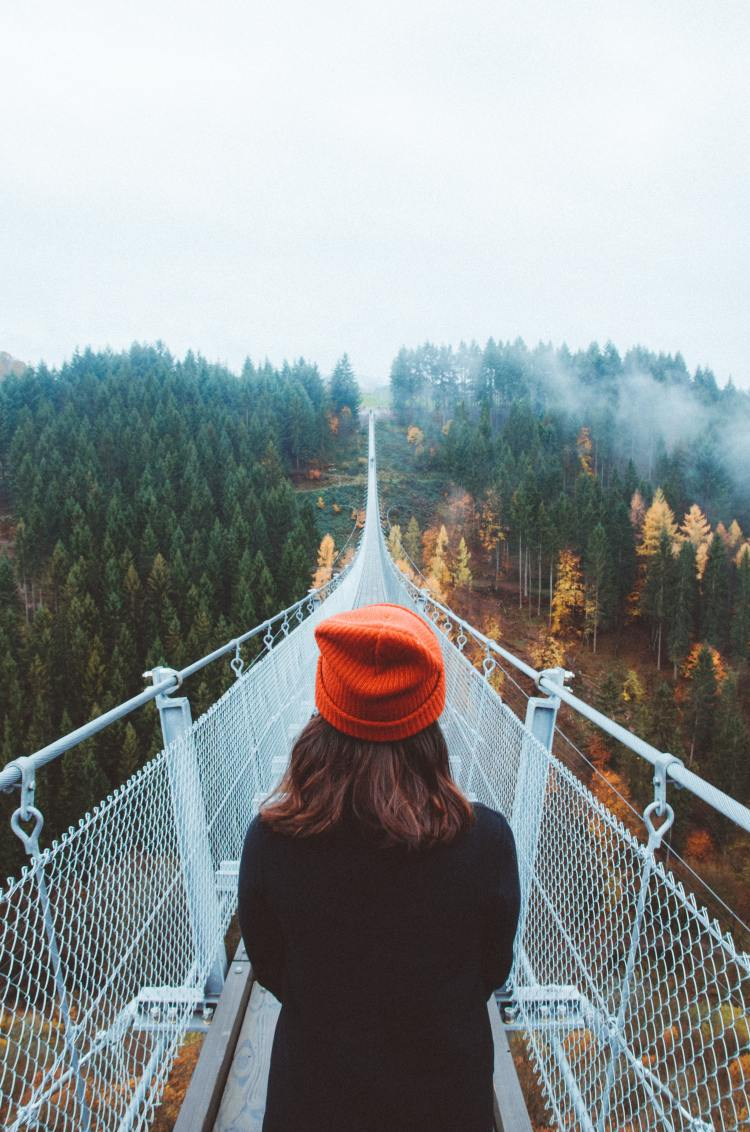 Woman starting a long journey acorss a bridge.